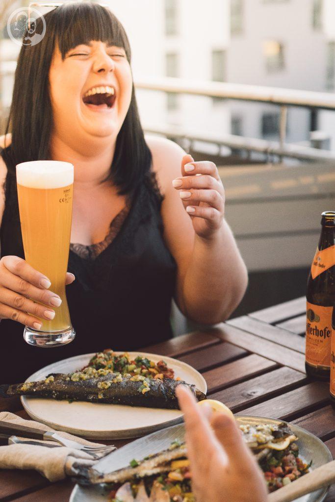 Gast lacht mit Bierglas in der Hand