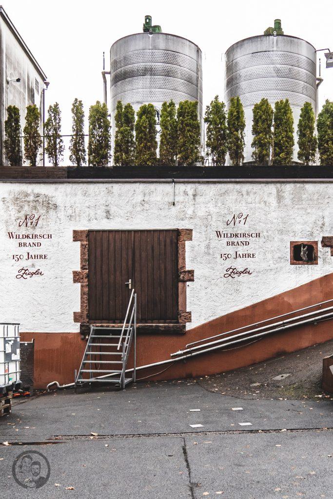 Brennerei Ziegler 3 | Torsten und ich haben in den letzten Jahren eine waschechte Sammelleidenschaft für Hochprozentiges entwickelt. Während Torsten ein ganz großer Fan von Whisky und Bränden verschiedenster Art ist, liegt bei mir der Fokus auf Rum und Gin. Umso mehr haben wir uns gefreut, dass wir Anfang Dezember eine der besten Brennereien Deutschlands besuchen durften - die Brennerei Ziegler! Da wir als Dankeschön auch etwas Leckeres mitbringen wollten, hatten wir eine Kiste Pralinen mit Schuss im Gepäck. Natürlich mit einem grandiosen Brand, Likör und Geist von der Brennerei Ziegler.