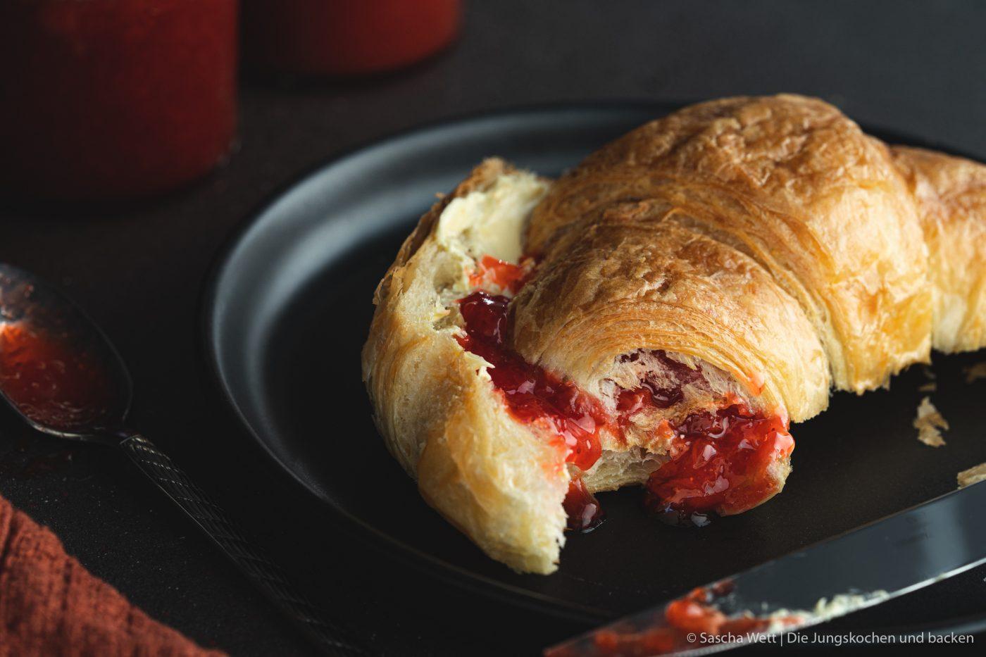 Rhabarber-Erdbeerkonfitüre auf Croissant, angebissen