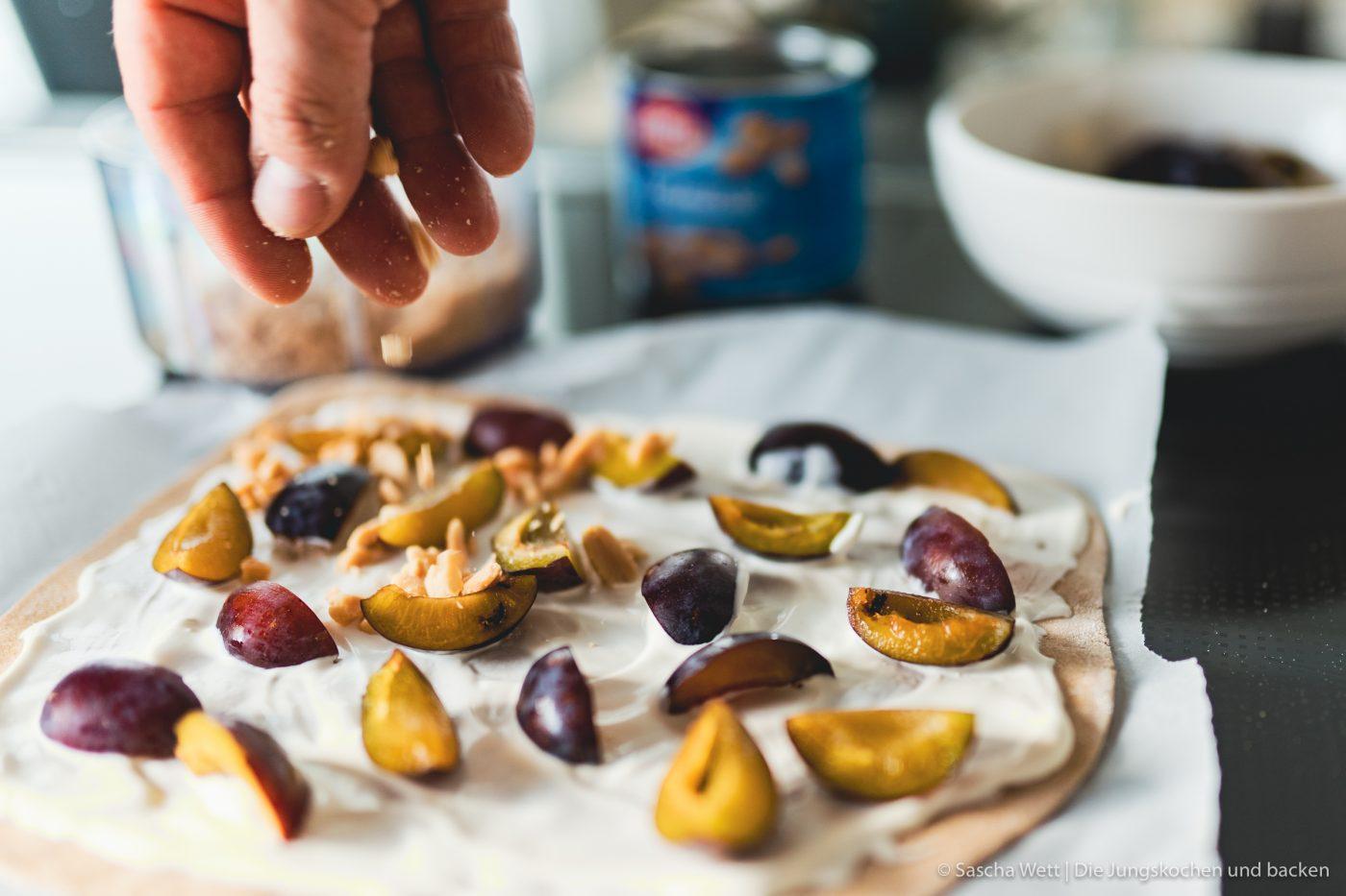Vollkorn-Flammkuchen mit Erdnüssen, Pflaumen, Honig in Zubereitung