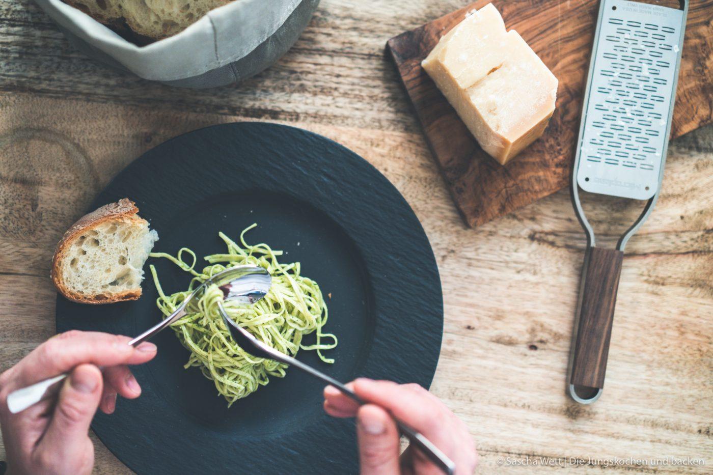 Spaghetti auf Teller. Spaghetti werden mit Gabel und Löffel aufgerollt