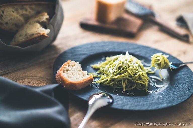 Pesto Spaghetti auf schwarzem Teller mit Brot auf dem Rand