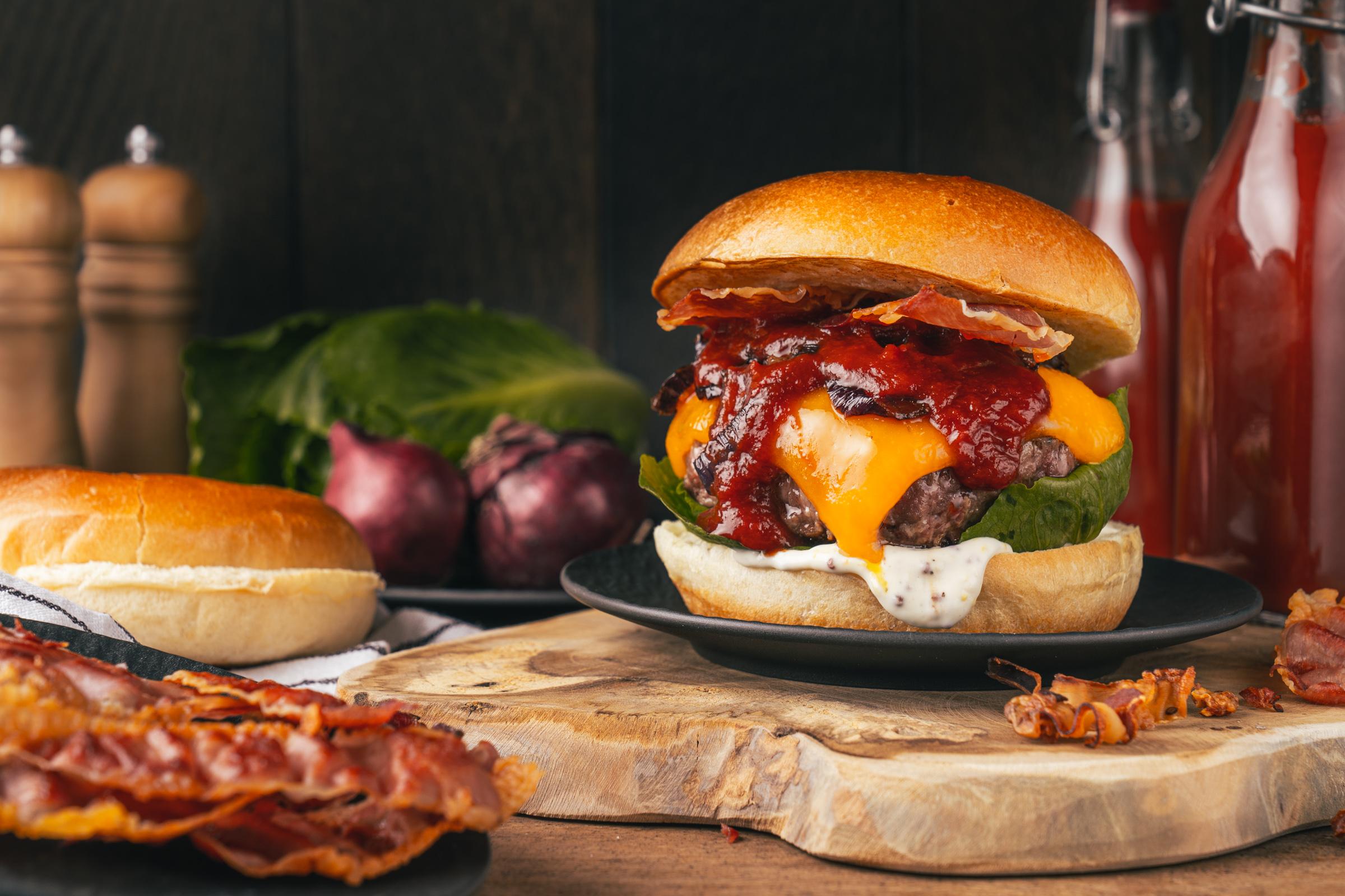 Rezept für einen klassischen BBQ-Cheeseburger, den wir mit einer dicken Scheibe Cheddar belegt haben. Getoppt von unserer BBQ-Sauce und Bacon, einfach perfekt.