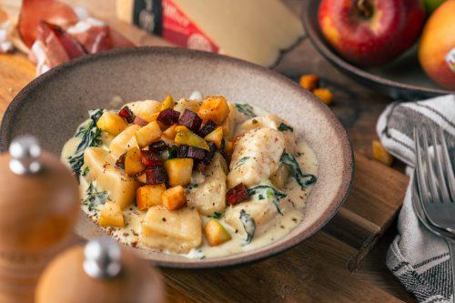 Rezept für selbstgemachte Gnocchi in einer cremigen Käsesauce mit Apfel-Speck-Crunch. Das Highlight sind die leckeren Südtiroler Spezialitäten mit Gütesiegel!