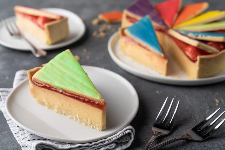 Rezept für eine Zitronentorte. Mürbeteig, eine zitronige Puddingcreme und als Topping ein Wild Berry-Guss! Da i-Tüpfelchen sind die Keksdeckel im Regenbogendesign.